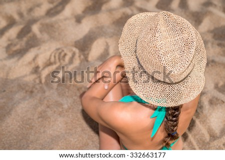 Girl seated on the beach with a straw hat, beach holidays concept, Sardinia Italy