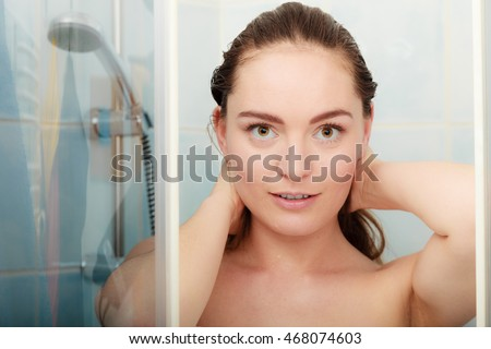 Girl showering in shower cabin cubicle enclosure. Young woman taking care of hygiene in bathroom.