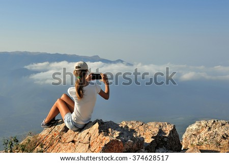 Girl sits on the top of the mountain and take pictures on the phone during a hiking trip, the concept of freedom