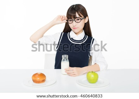 girl sitting in a classroom, apples and oranges arrayed on the desk as well as milk.