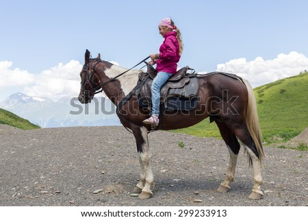 girl sitting on a horse in the mountains