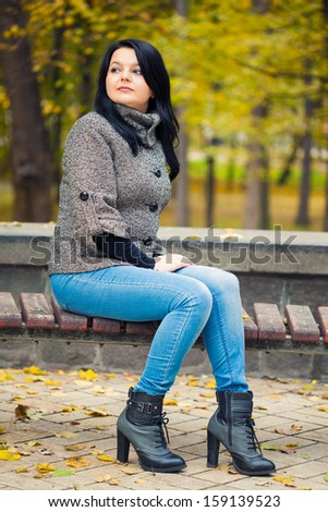 girl sitting on bench in autumn park