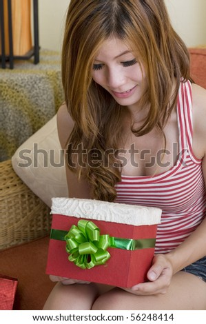 Girl sitting on sofa holding a gift box
