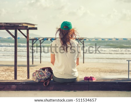 Girl sitting on the beach looking at the sea