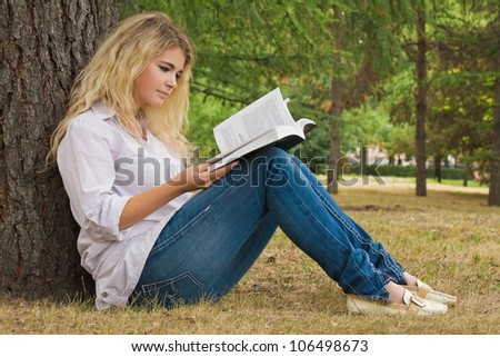 Girl sitting under the tree reading a book, horizontal