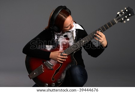 Girl sitting with bass guitar and play music, gray background