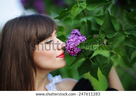girl smelling a purple lilacs in the spring in the park.