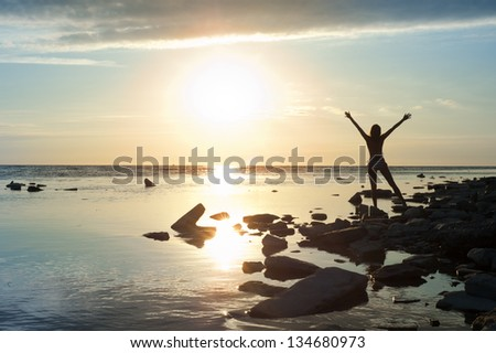 Girl standing arms outstretched at sunset
