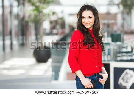 Girl standing in shopping mall, looking at camera and smiling. Holding hands on jeans. Wearing red blouse and jeans. Indoor, shopping mall background