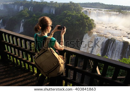 girl taking a photo of Iguassu waterfall with smartphone