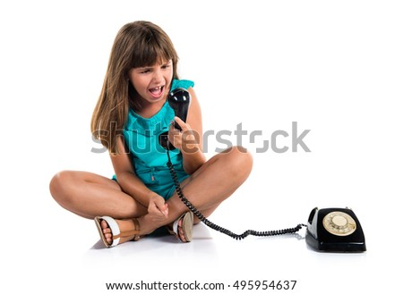 Girl talking to vintage phone and shouting