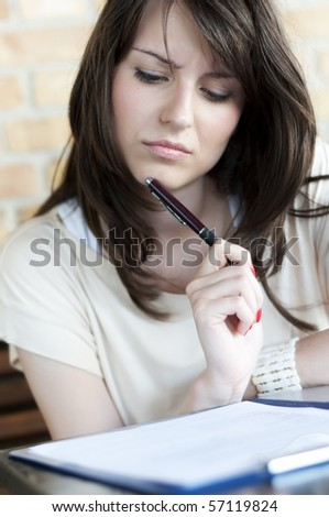 Girl thinking and looking at the paper on the desk holding a pen