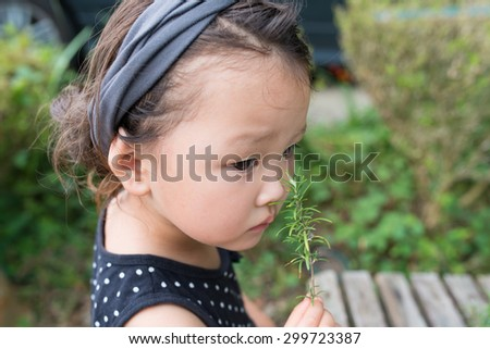 Girl to smell the scent of rosemary