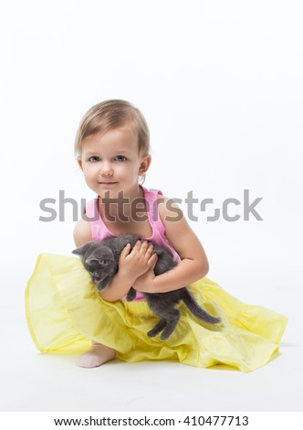 Girl two years playing with a kitten