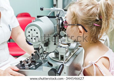 Girl undergoing eye is at examination in clinic with special equipment.