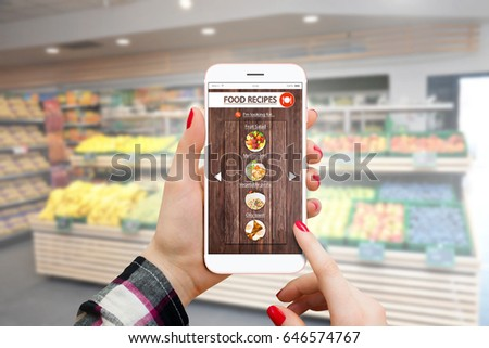Girl using smartphone in supermarket and buying groceries to prepare meal