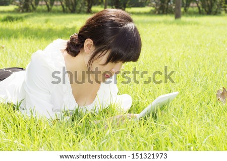 girl using tablet pc on the grass