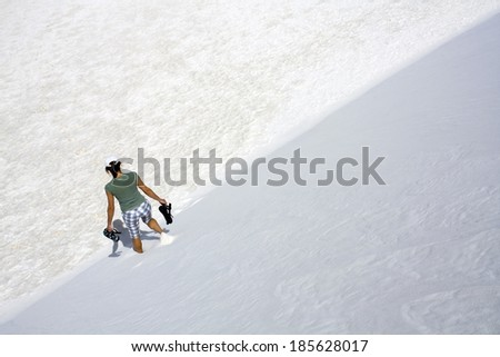 Girl walking down the dune in White Sand Dunes National Park in New Mexico.