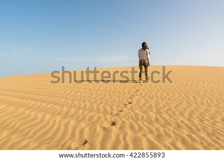 Girl walking on sand dunes in Gran Canaria, Spain