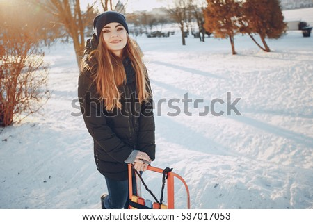 girl walking on snow-covered town, drinking coffee, photographed on the phone and riding on a sled