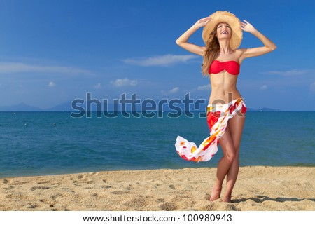 Girl wearing bikini and hat and posing at the sandy beach