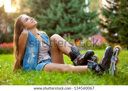 girl wearing roller skates sitting on grass in the park