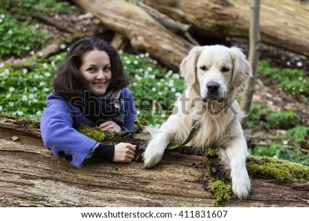 girl with a dog golden retriever look out from behind a tree