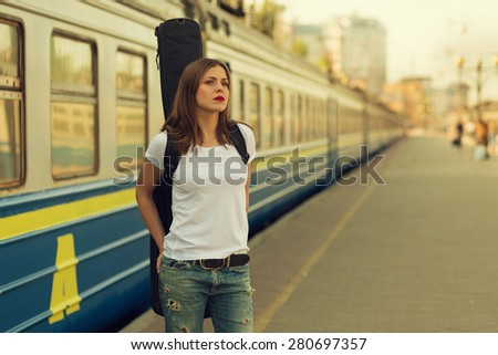Girl with a guitar at train station. Retro toned image