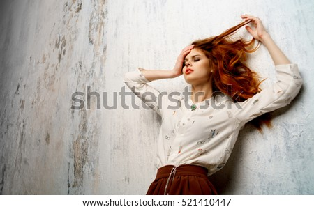 Girl with beautiful hairstyle on a light background. Beautiful light background. Red hair. laying