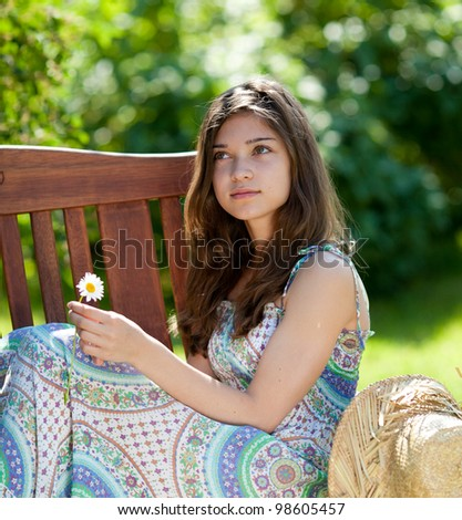 Girl with camomile or oxeye daisy flower sitting outdoor in summer day