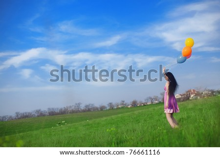 Girl with colorful balloons in the field against the blue sky