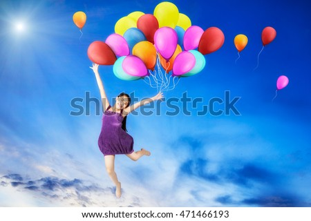 Girl with colorful balloons jumping and the blue sky