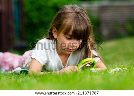 Girl with magnifying glass taking a close look at a flower.