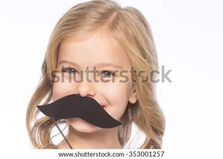 Girl with paper moustache. Little girl is smiling while upholding decorative paper moustache.