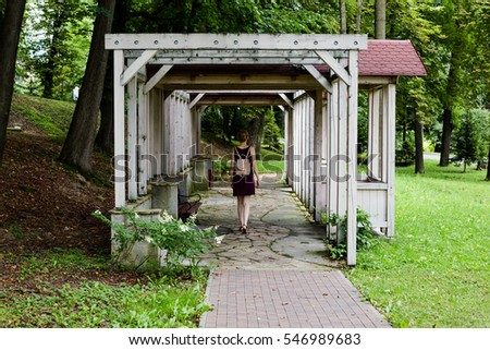 Girl with pink rucksack is walking inside the arbour.