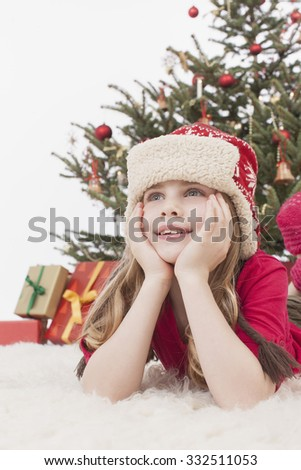 Girl with Santa hat lying on carpet, Christmas tree and gift in background
