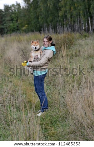 Girl with shiba inu dog in the autumn forest