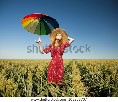 Girl with umbrella at corn field
