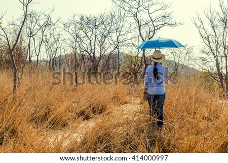 girl with umbrella at grass field