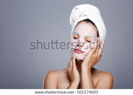 Girl with wrapped hair with towel. Closed eyes, touching skin covered by mask. Girl with white face, has mask on face. Head and shoulders, studio, indoors