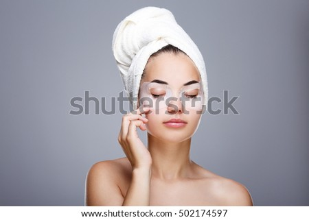 Girl with wrapped hair with towel. Closed eyes, touching skin under eyes. Girl with special mask on eyes. Head and shoulders, studio, indoors