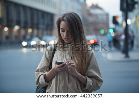 girl writes something in social networks standing on the street in the evening