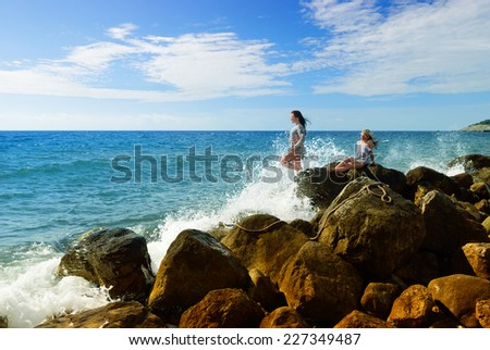 Girls after a shipwreck sitting on the rocks