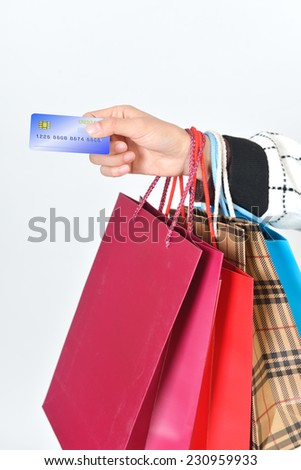 Girls hand over credit cards. Hands and shopping bags feature