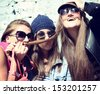 Girls having fun together outdoors and making moustache of hair, lifestyle theme, toned image - stock photo