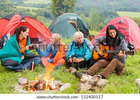 Girls on vacation camping with tents listening girl playing guitar