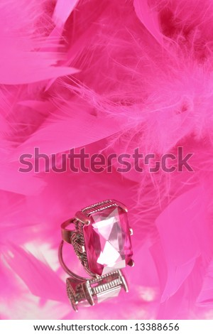 glamorous diamond ring on vanity mirror with a pink feather boa in the background