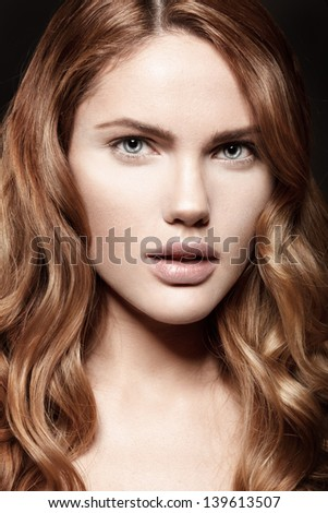 Glamour portrait of beautiful woman model with fresh daily makeup and romantic wavy hairstyle.  Fashion shiny highlighter on skin, sexy gloss lips makeup and dark eyebrows