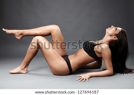 Glamour profile of perfect exotic dancer in sexy lingerie lying on the ground.