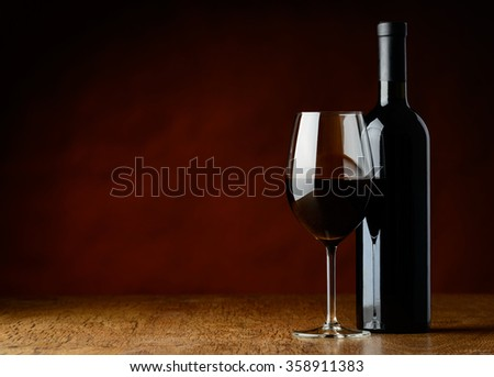 Glass and bottle of red wine on dark background and on a wooden table